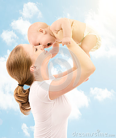 Happy family. Mother kissing baby in the sky