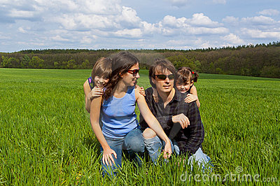 Happy family outdoors on green field
