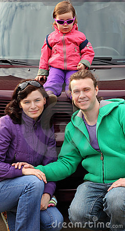 Happy family in outwear near car