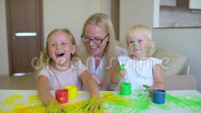 Happy family paints colors. Happy family paints colors. Mother and daughter having fun and paint each other`s on faces. At home. Family jokes. Slow motion stock video