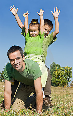 Happy family playing on the meadow