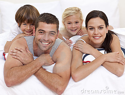 Happy family playing in parent s bed