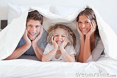 Happy family posing under a duvet