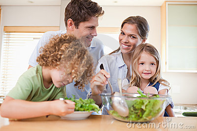 Happy family preparing a salad