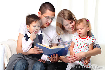 Happy family reading a book on sofa