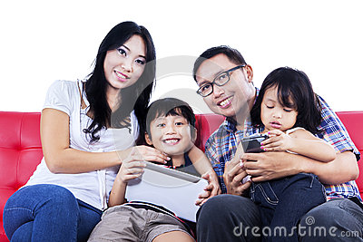 Happy family on red sofa - isolated