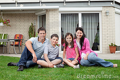 Happy family relaxing in backyard of new home