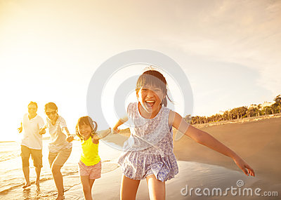 Happy family running on the beach Stock Photo