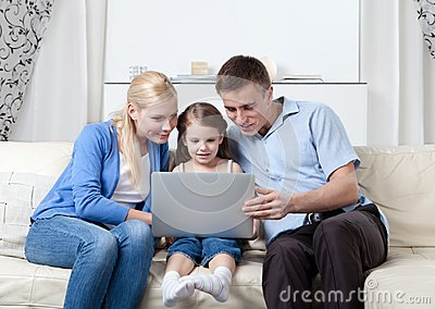 Happy family sit on the couch with laptop