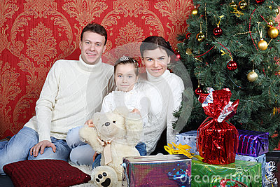 Happy family sit on floor with gifts near Christmas tree