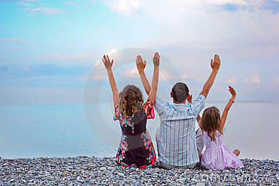 Happy family sitting on beach lifted hand