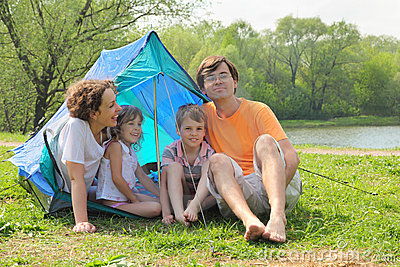 Happy family sitting in blue tent