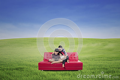 Happy family sitting on a couch on a green meadow