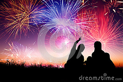 Happy family sitting on floor and watching the fireworks Stock Photo