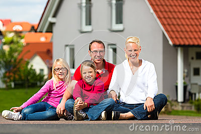Happy family sitting in front of home