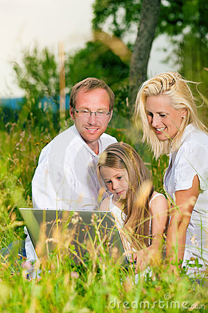 Happy family sitting in meadow
