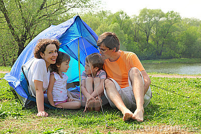 Happy family sitting in tent on lawn