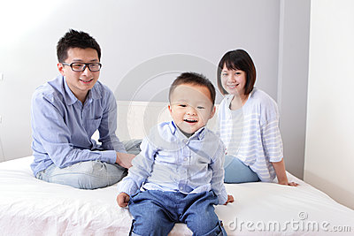 A happy family sitting on white bed