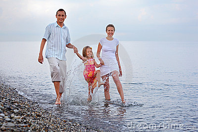 Happy family splashes feet water on beach