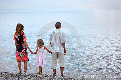 Happy family standing on beach in evening