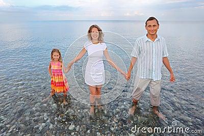 Happy family standing knee-deep in sea on beach