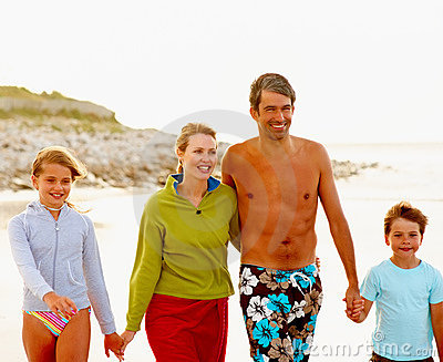 Happy family strolling on the sea shore