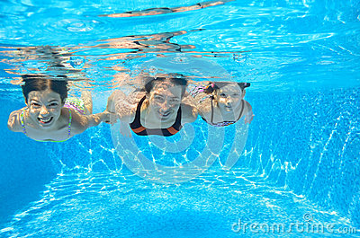 Happy family swim underwater in pool
