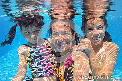 Happy family swim underwater in pool