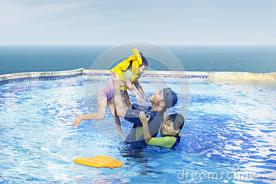 Happy family swimming on the pool