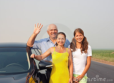 Happy family of three  by car