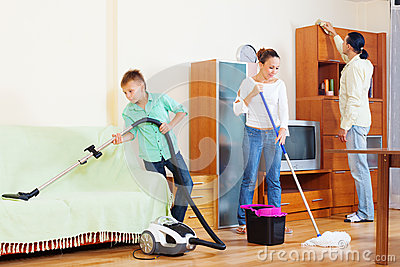 Happy family of three cleaning  in living room