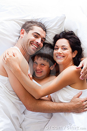 Happy family together in bed