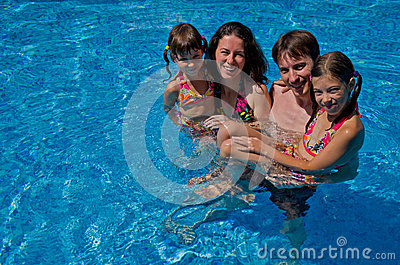 Happy family with  two kids in swimming pool