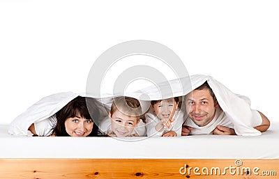 Happy family under blanket