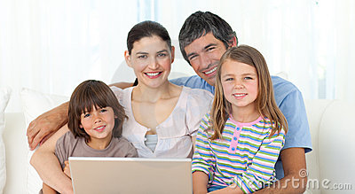 Happy family using a laptop on the sofa