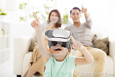 Happy family with virtual reality headset in living room Stock Photo