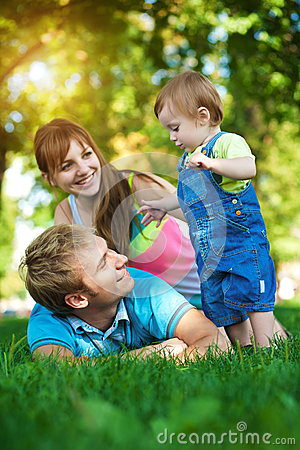 Happy family are walking in the green summer park