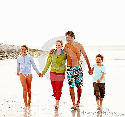Happy family walking on the sea shore
