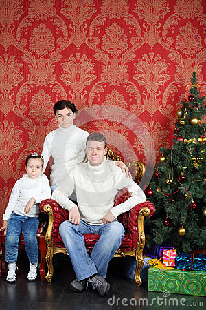 Happy family in white sweaters and jeans near Christmas tree
