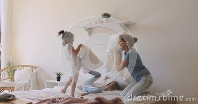 Happy mom and children daughters playing pillow fight on bed stock video