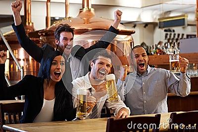 Happy fans watching TV in pub cheering