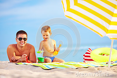 Happy father and child having fun on the beach