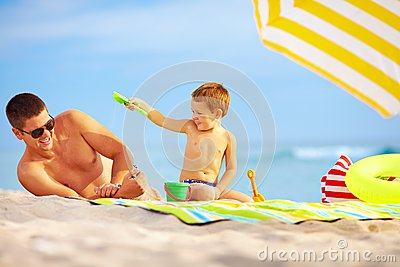 Happy father and child playing on the beach
