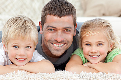 Happy father and children lying on the floor