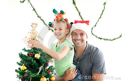 Happy father and daughter decorating the tree