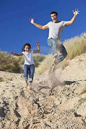 Happy Father and Daughter Jumping At Beach