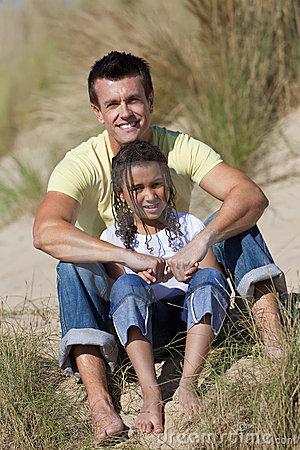 Happy Father and Daughter Sitting At Beach