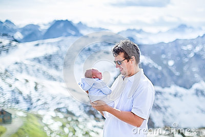 Happy father with his newborn baby in mountains