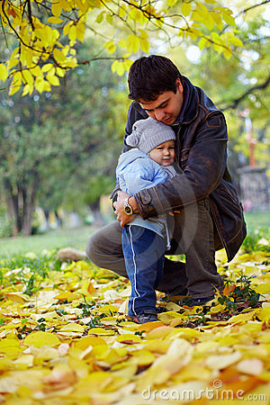 Happy father hugging little son in autumn park