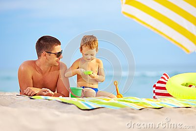 Happy father and kid playing on the beach